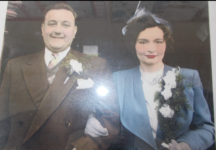 Man posing with his wife for wedding photograph in vintage photo